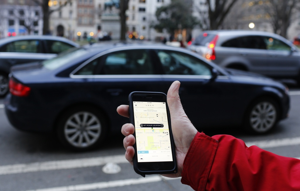 An Uber application is shown as cars drive by in Washington, D.C. on March 25, 2015.