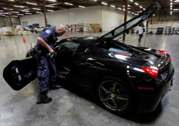 U.S. Customs and Border Protection officer Paulo Zanetti, right, checks the interior of gas tanks, next to a 2010 Ferrari 458 Italia