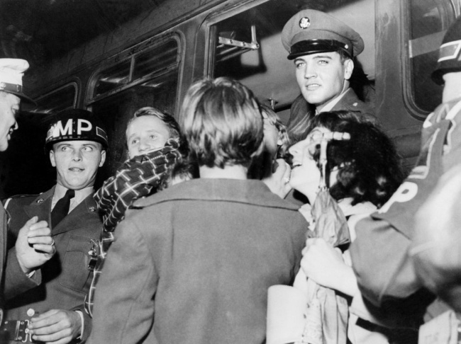 Rock'n roll legend Elvis Presley (C) is surrounded by fans after a concert, in 1958. (Photo credit should read -/AFP/Getty Images)