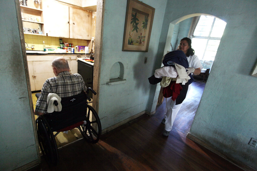 A home health aide carries laundry for a client in Miami, Fla., December 14, 2009. How to deal with aging loves ones can be tough for families from countries where tradition dictates that the elderly are cared for at home, but economic reality dictates otherwise.