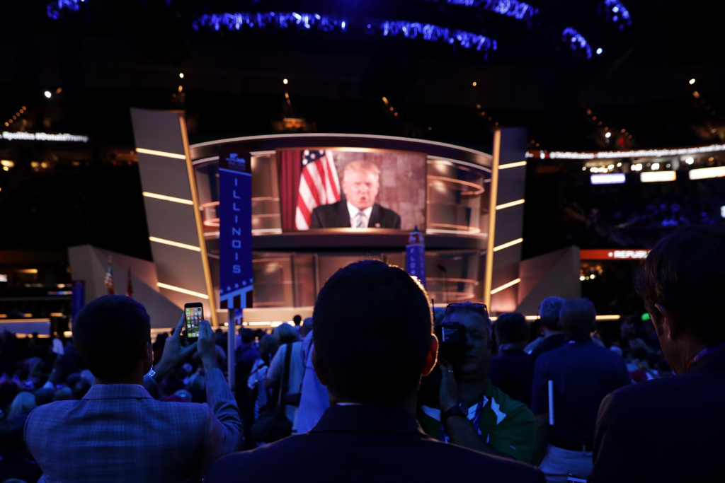 CLEVELAND, OH - JULY 19: Republican presidential candidate Donald Trump is seen speaking on a screen from New York City, on the second day of the Republican National Convention on July 19, 2016 at the Quicken Loans Arena in Cleveland, Ohio. Republican presidential candidate Donald Trump received the number of votes needed to secure the party's nomination. An estimated 50,000 people are expected in Cleveland, including hundreds of protesters and members of the media. The four-day Republican National Convention kicked off on July 18.  (Photo by Chip Somodevilla/Getty Images)