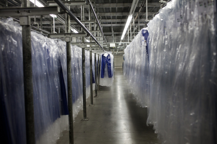 Antonio Herdandez, left, and Angel Guerrero spread fabric at the Karen Kane warehouse. The layered stack of fabric is then cut to make different components of the clothing.