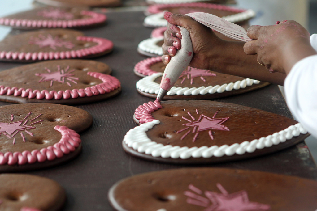 An employee decorates gingerbread hearts to be sold at Oktoberfest in Aschheim, Germany on August 6, 2010.