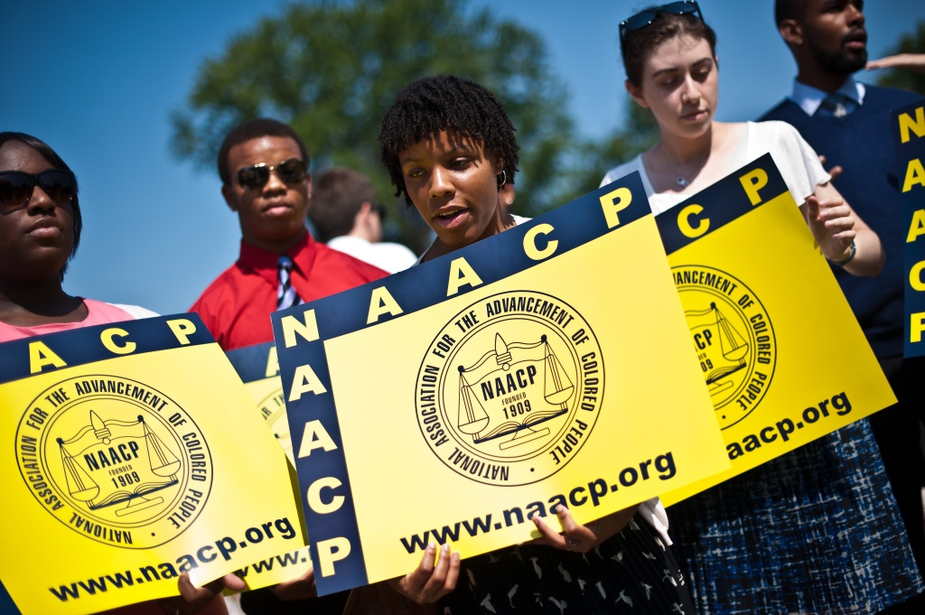Members of the National Association for the Advancement of Colored People (NAACP) hold signs in front of the US Supreme Court in Washington on June 25, 2013. The court struck down a key part of the Voting Rights Act, which guards against racial discrimination in US states with a segregationist past. In a hotly anticipated decision, the court ruled 5-4 that Section 4 of the 1965 law was unconstitutional, calling on Congress to redefine which states must seek government approval for changes to their electoral codes.
