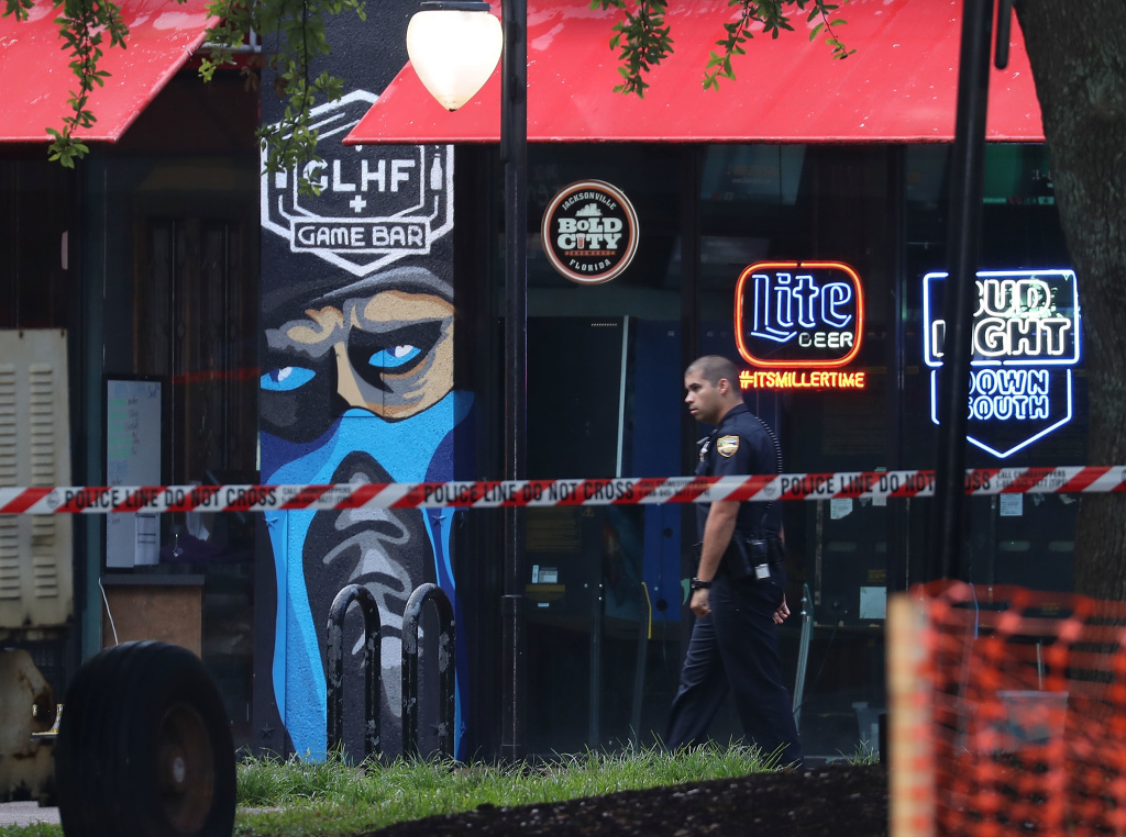 A police officer walks past the GLHF Game Bar where three people including the gunman were killed at Jacksonville Landing on Sunday in Jacksonville, Fla.