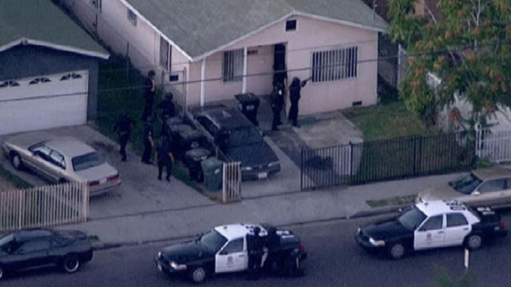 Police surround a home where they believe an armed suspect shot at an LAPD officer and a county probation officer in South Los Angeles on Tuesday night.