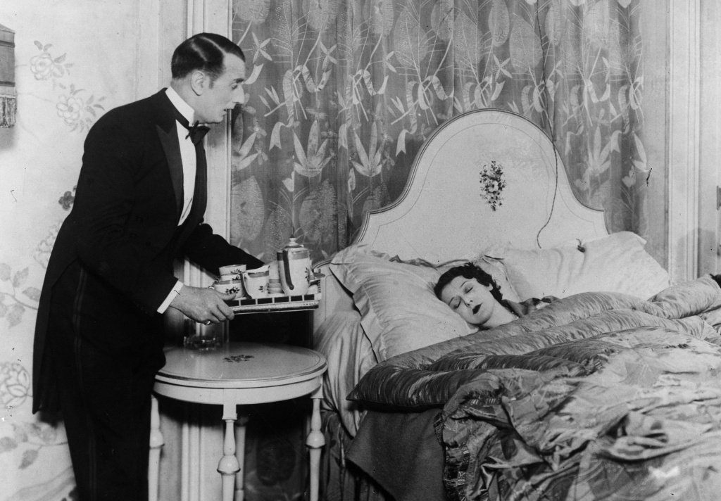 circa 1930:  A butler brings his mistress breakfast in bed.