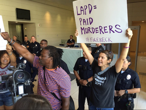 Protesters block the lobby of LAPD headquarters on Monday, following the fatal police shootings of two men over the weekend.
