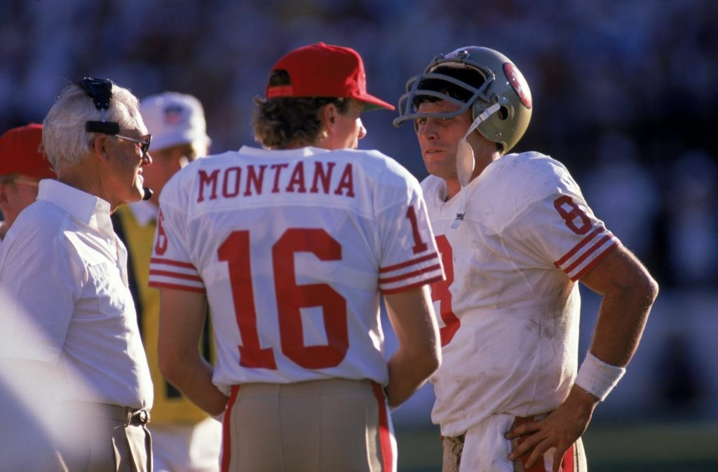 Quarterbacks Steve Young #8 and Joe Montana #16 of the San Francisco 49ers discuss strategy with head coach Bill Walsh during the game against the Phoenix Cardinals at Sun Devil Stadium on Novemer 6, 1988 in Tempe, Arizona. The Cardinals won 24-23.