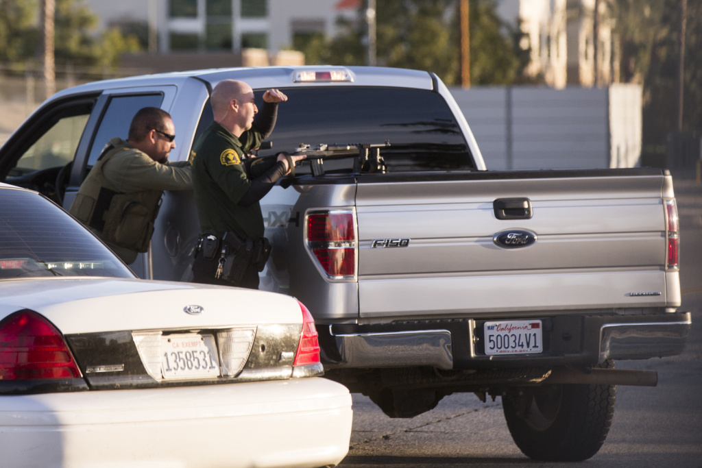 San Bernardino Sounty Sheriff's deputies draw their guns on South Mountain View Avenue near San Bernardino Avenue in Redlands, Calif. on Wednesday, Dec. 2, 2015 during an active shooter situation following a mass shooting at the Inland Regional Center.