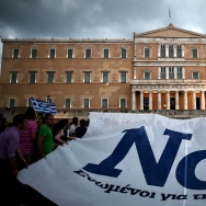 """Pro-euro protesters hold a banner reading ''YES"""" during a demonstration in front of the parliament in Athens on June 30, 2015."""