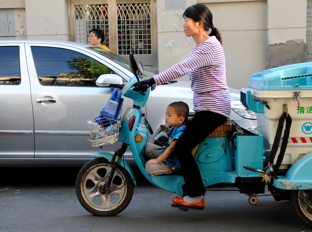 This picture taken on September 13, 2012 shows a family riding an electric-tricycle along a street in Tianjin. China's elderly face increasing uncertainty three decades since the one-child policy took hold, with no real social safety net, the law has left four grandparents and two parents with one caretaker for old age -- and bereaved families with none.