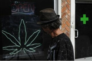 A man walks past a medicinal marijuana dispensary in Los Angeles, CA on November 2, 2010. Although voters rejected Prop 19, marijuana will still be legal for medical users.