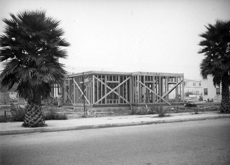 A woman, possibly Mrs. Morton, stands by a home under construction in Beverly Hills. Posters for the plumber, lumber yard and construction company are posted around the site which is framed by two palm trees.
