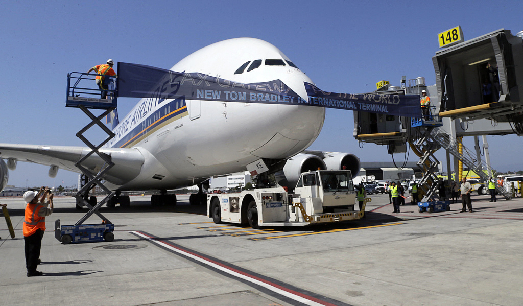 A Singapore Airlines Airbus 380,  Flight 12 from Singapore to Los Angeles, breaks a ribbon in the ceremonial grand opening of the Tom Bradley International Terminal at Los Angeles International Airport Wednesday, Sept. 18, 2013.