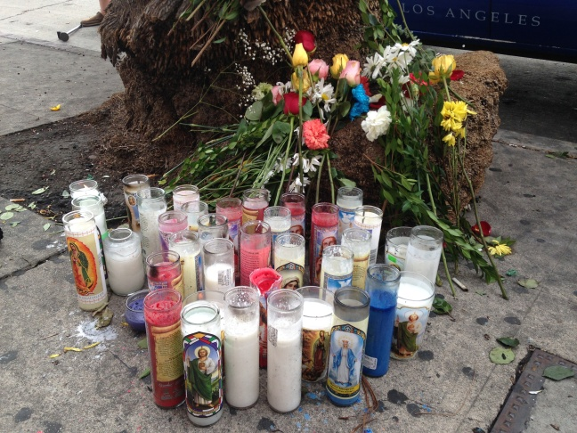 Candles at the curbside pickup spot on Olympic Boulevard in Koreatown for the tour bus company that was involved in a crash that left 13 dead.