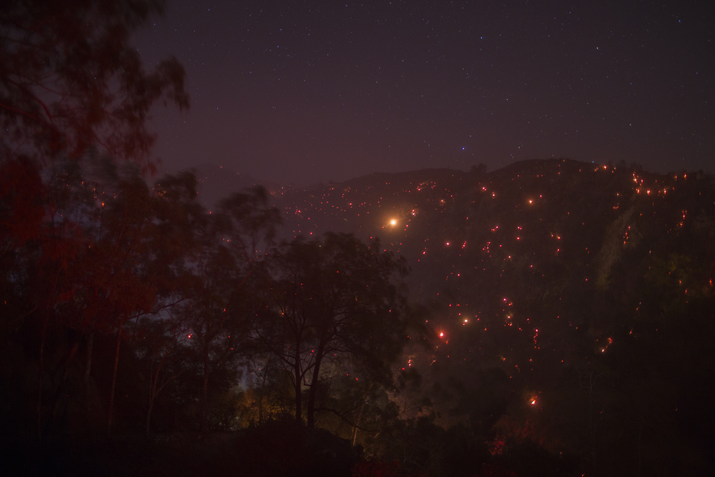 A smoldering mountainside is seen under a starry sky at the Thomas Fire on December 16, 2017 in Montecito, California.