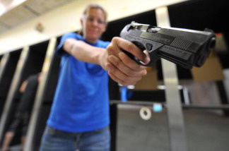 An employee of the Project Y2000 firing range checks the balance of a handgun at the range in El Cajon, Southern California, on April 21, 2009.