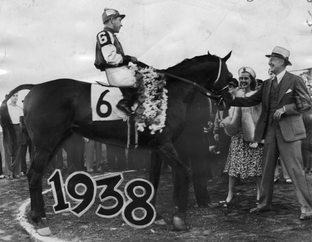 Seabiscuit is shown in the winner's circle after winning the initial running of the $50,000 Hollywood Gold Cup race on July 18, 1938. George Woolf is the jockey, with his owner, Charles S. Howard, and Anita Louise paying homage to the great champ.