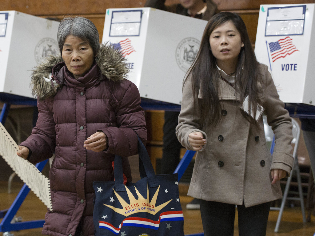 Ping Chan (right), a Chinese-language interpreter, assists a voter in Brooklyn, N.Y., on Nov. 8, 2016.