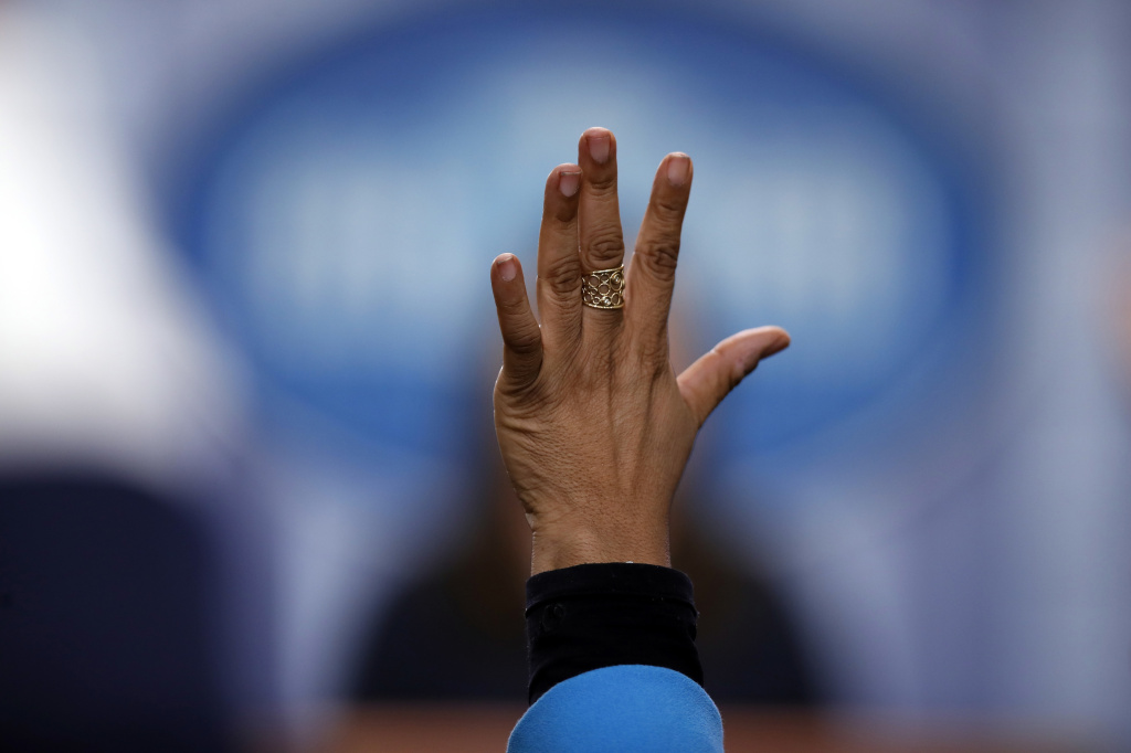 Reporter April Ryan raises her hand during a press briefing at the White House in 2017. Her pointed questioning has often earned her the ire of the Trump administration's communications team, as she writes in <em>Under Fire</em>.