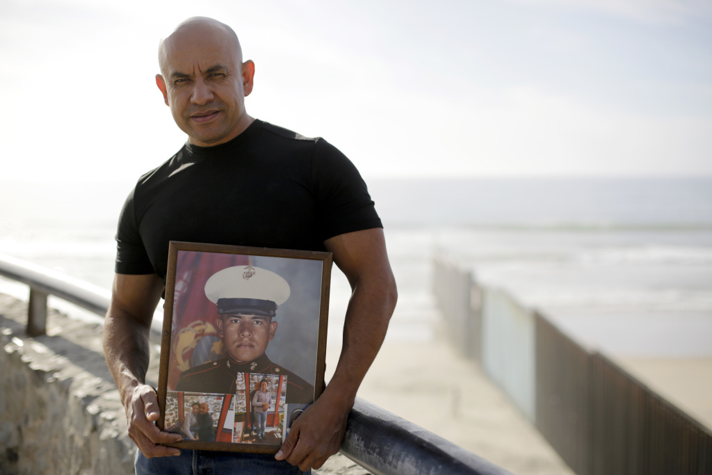 U.S. Marine Corps veteran Antonio Romo on Feb. 13, 2017, holds a picture of himself taken from his days at boot camp, as he poses for a portrait next to the U.S. border wall on the beach in Tijuana, Mexico. Romo is part of a group of dozens of U.S. military veterans who were deported after criminal convictions and for years have fought to be allowed to return.