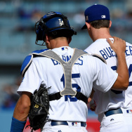 Relief pitcher Walker Buehler #64 is consoled by Austin Barnes #15 of the Los Angeles Dodgers after giving up a grand slam home run in the eighth inning of the game to Mark Reynolds #12 of the Colorado Rockies at Dodger Stadium on September 10, 2017 in Los Angeles, California.