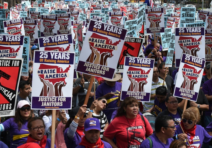 A group of janitors estimated by police to number 3,000 march through downtown streets during a demonstration over wages with the threat to strike in Los Angeles on April 29, 2016.