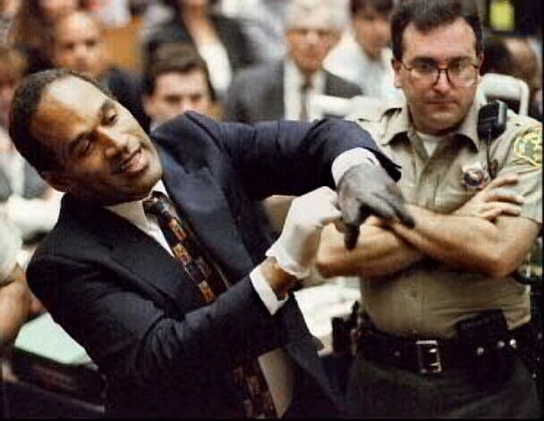 O.J. Simpson struggling to put on the infamous bloody glove in court.