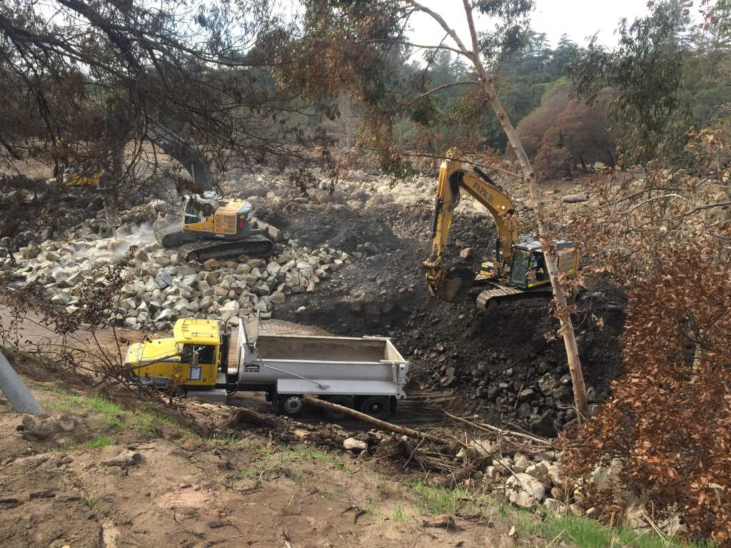 To clear the basin of boulders, crews are using three machines. One moves the rocks towards the second one, which breaks them into smaller rocks. The third loads up trucks to take them away.