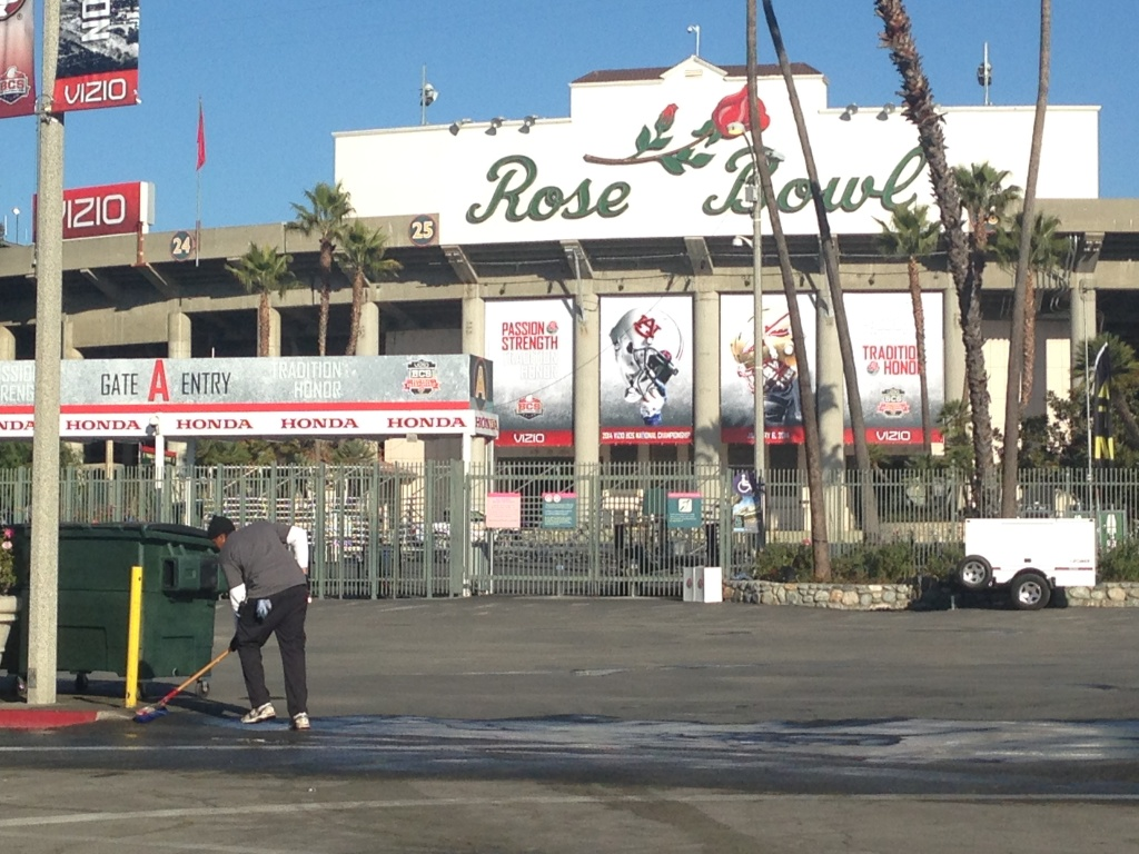 A worker cleans up the Rose Bowl stadium grounds on the day before the BCS Championship game.