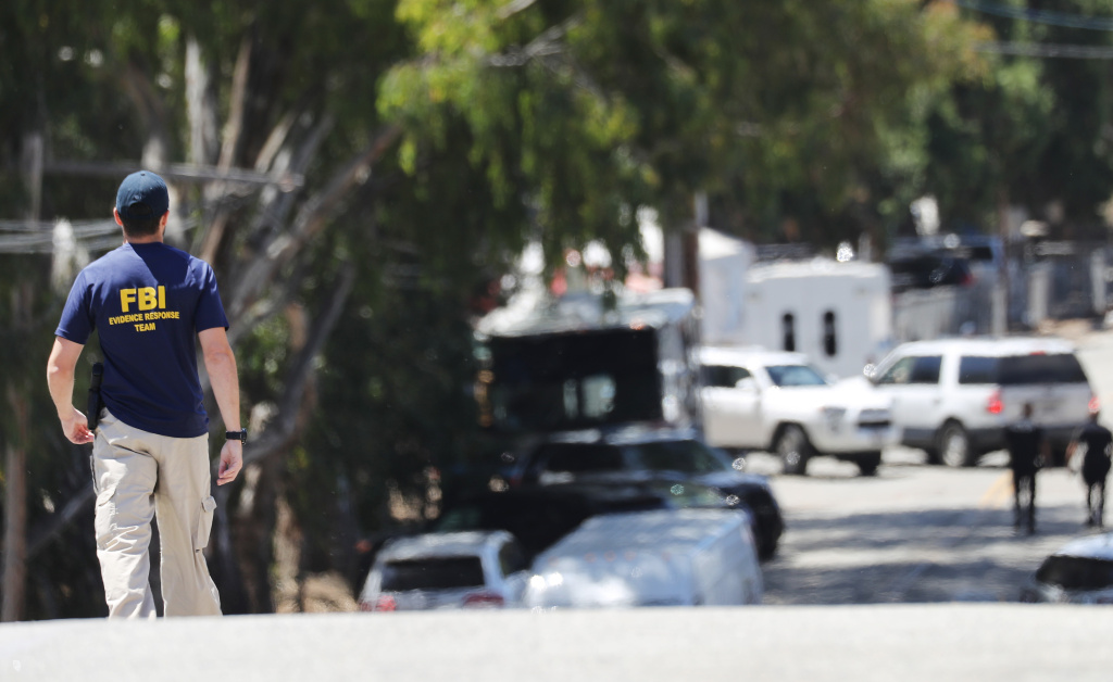 GILROY, CALIFORNIA - JULY 29: An FBI agent walks toward the site of the Gilroy Garlic Festival after a mass shooting there yesterday on July 29, 2019 in Gilroy, California.  Three victims were killed and at least a dozen were wounded before police officers killed the suspect. (Photo by Mario Tama/Getty Images)