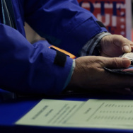 A voter shows his photo identification to an election official Feb. 26 at an early voting polling site, in Austin, Texas.