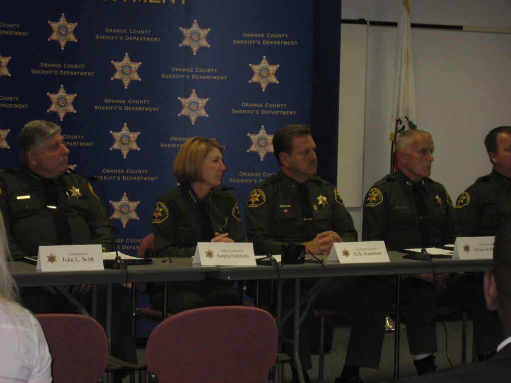 Sheriff Sandra Hutchens is surrounded by her command staff as she speaks with reporters in Santa Ana about the milestones of her first year in office.