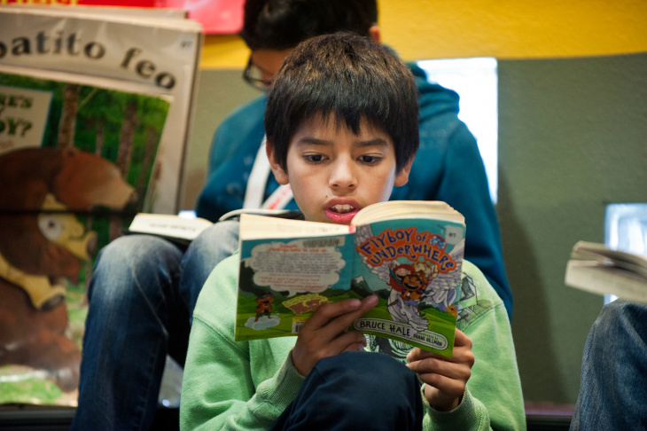 Trinity Street Elementary fifth graders Laura Flores, left, and Aylin Guzman read a book in the children's section of the Junipero Serra Library on Thursday morning during a school visit on Thursday morning, March 21.