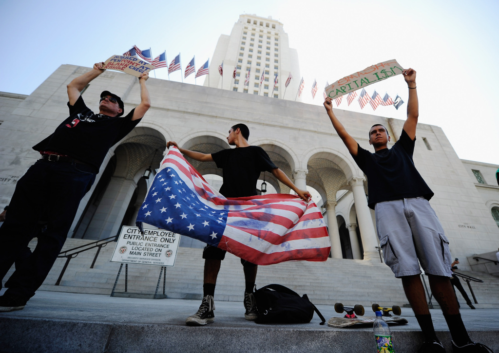 LOS ANGELES, CA - OCTOBER 01:  Protesters hold signs after a march to Los Angeles City Hall during the