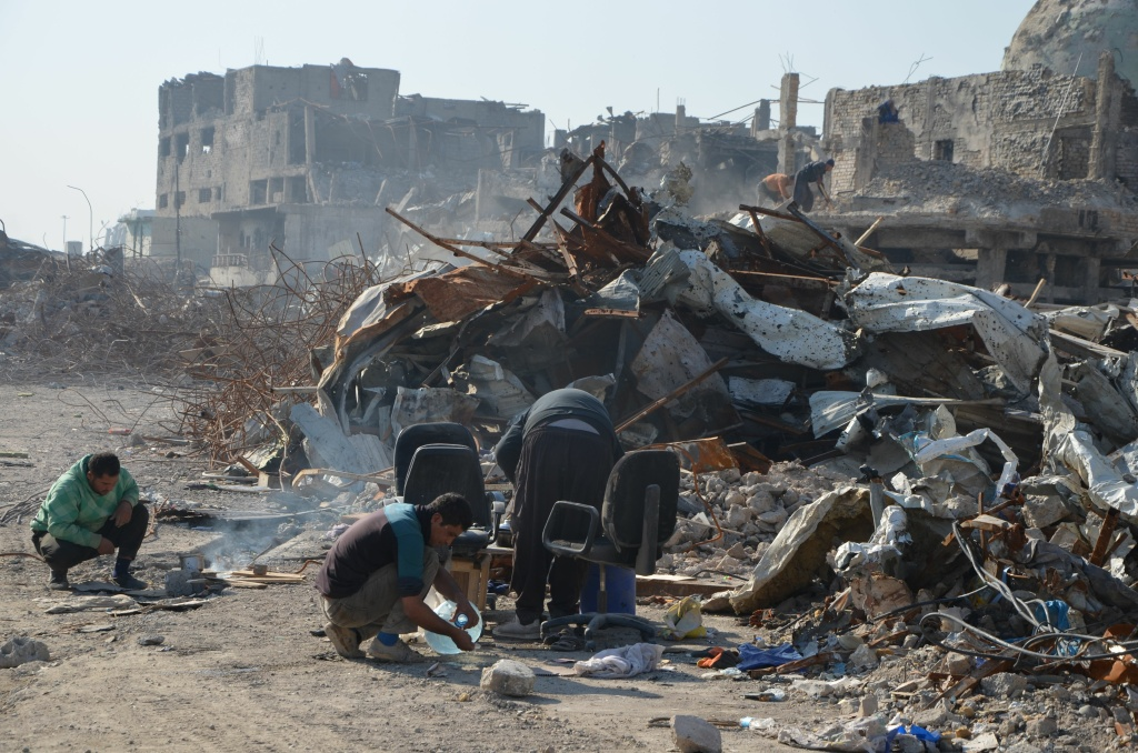 A picture taken on December 16, 2017 shows Iraqi volunteers salvaging and cleaning up the debris and destruction in the Bab al-Saray area in the old city of the northern Iraqi city of Mosul.