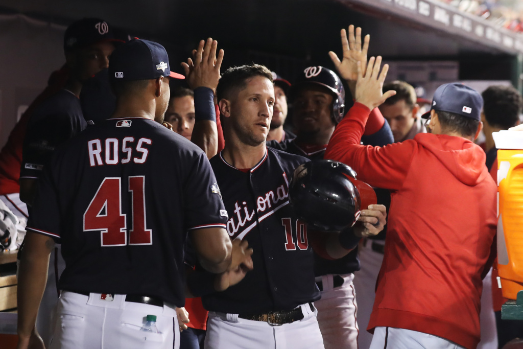 Yan Gomes #10 of the Washington Nationals celebrates in the dugout after scoring in the first inning against the St. Louis Cardinals during game four of the National League Championship Series at Nationals Park on October 15, 2019 in Washington, DC.