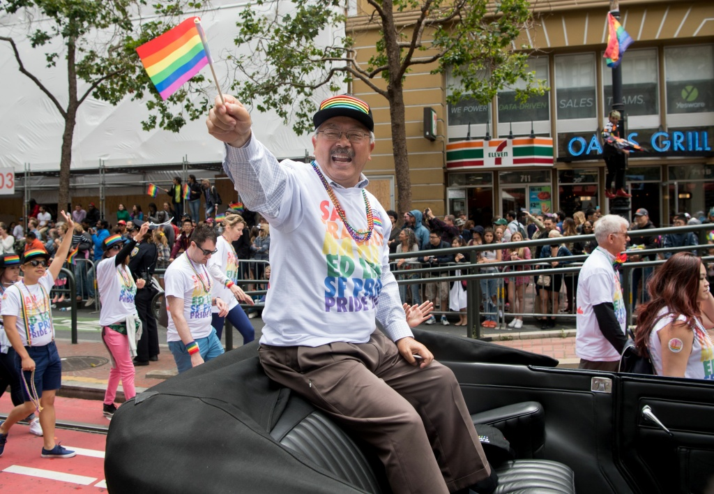 San Francisco Mayor Ed Lee waves to a cheering crowd along the San Francisco Pride parade route in San Francisco, California on June 25, 2017.