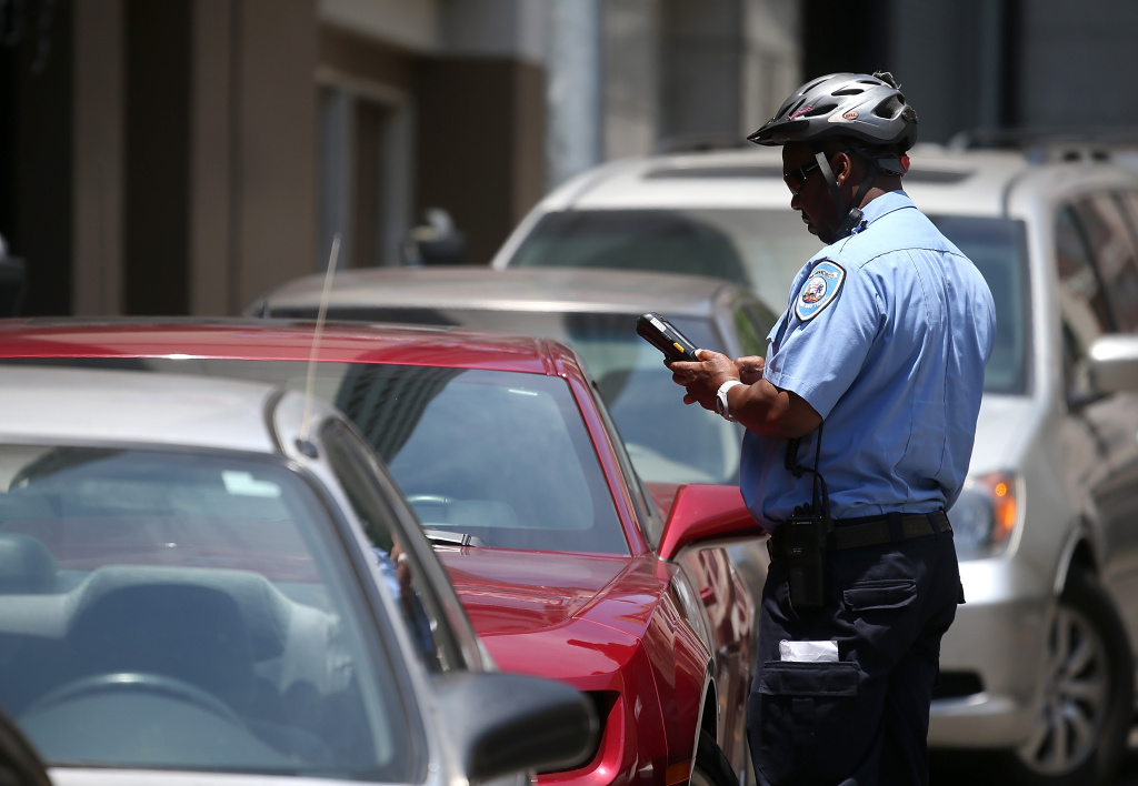 A Municipal Transportation Agency parking control officer writes a parking ticket for an illegally parked car.