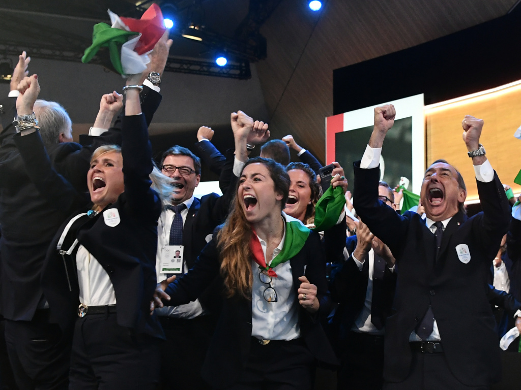 Members of the delegation from Milan and Cortina d'Ampezzo react after the Italian cities were named to host the 2026 Olympic Winter Games.