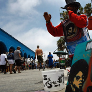 A painting of Michael Jackson awaits sale as artist and street performer Tony Conscious sings Michael Jackson hits at Venice Beach on June 28, 2009 in Los Angeles, California. Jackson, 50, the iconic pop star, died after going into cardiac arrest on June 25, 2009 in Los Angeles, California.