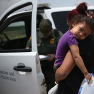 A mother and child, 3, from El Salvador await transport to a processing center for undocumented immigrants after they crossed the Rio Grande into the United States on July 24, 2014 in Mission, Texas. One teenage boy from Guatemala has taken his case to L.A. Superior Court in his attempt to stay in the U.S., saying he left Guatemala after gang members broke his leg.