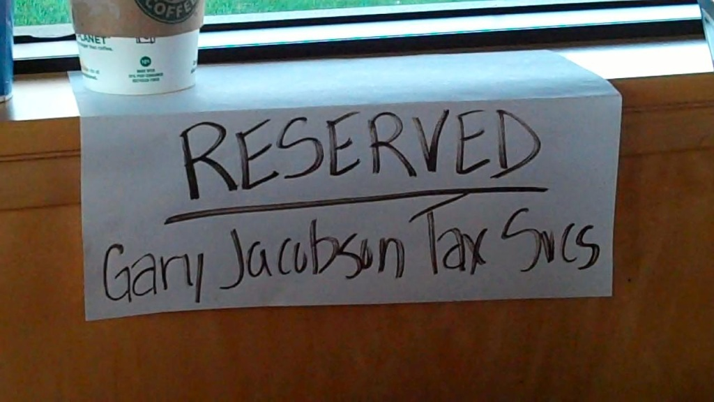 Gary Jacobson hangs this handmade sign over the window table at a Starbucks in Norwalk where he spent the day helping deaf and hard of hearing people prepare their taxes.