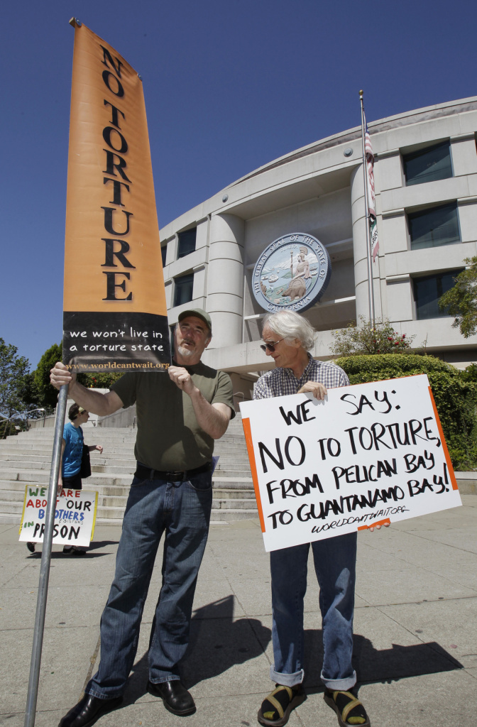 Demonstrators hold up signs during a rally in front of the State Building in San Francisco, Friday, July 1, 2011 to support prisoners at Pelican Bay State Prison.