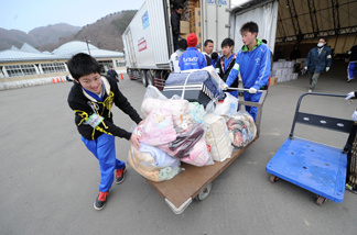 Volunteers push a trolley filled with blankets destined for displaced people in the city of Kamaishi in Iwate prefecture.