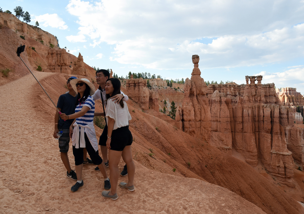 Visitors take a selfie on August 12, 2016 in front of hoodoos named Thor's Hammer and the Three Sisters along the Navajo Loop Trail in Bryce Canyon National Park, Utah.