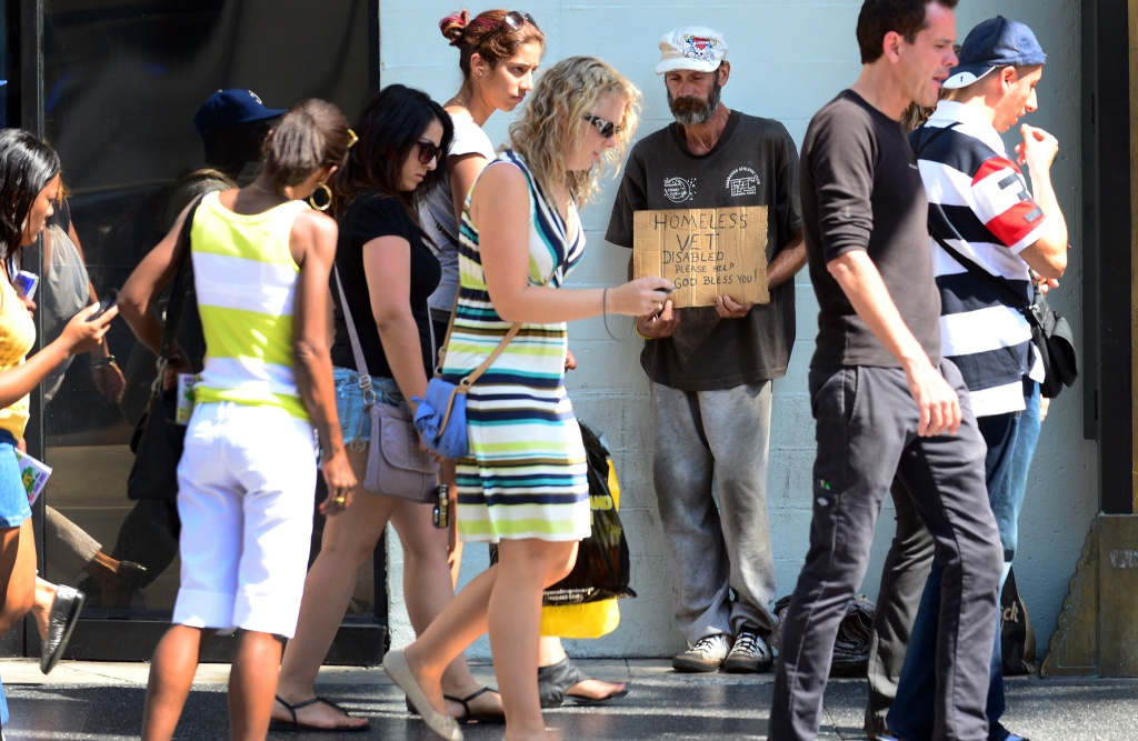 People walk past a homeless war veteran explaining his plight hoping for assistance while standing along Hollywood Boulevard in Hollywood, California, on August 22, 2012.