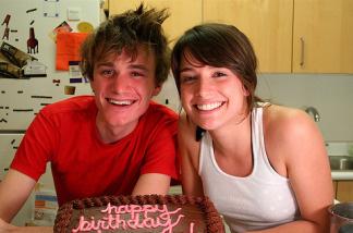 Friends bake a cake in their dorm.