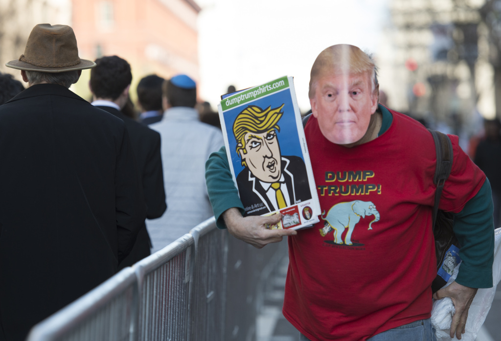A man protesting US Republican presidenial candidate Donald Trump walks next to the line of attendees entering Verizon Center during the AIPAC 2016 Policy Conference on March 21, 2016 in Washington, DC.